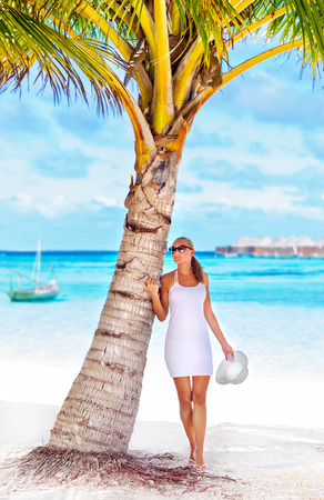 Sexy woman on the beach standing near palm tree, relaxation outdoors, luxury tropical resort, summer vacation on Maldives photo