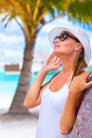 Portrait of pretty woman wearing white hat and sunglasses enjoying bright sun light, happy summer holidays, tropical resort on Maldives photo