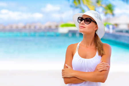 Closeup portrait of cute blond girl enjoying summer day on the beach, wearing white hat and stylish sunglasses, vacation concept photo