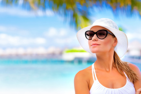 Closeup portrait of pretty woman standing on seashore and looking into the distance, enjoying beach resort on Maldives Stock Photo
