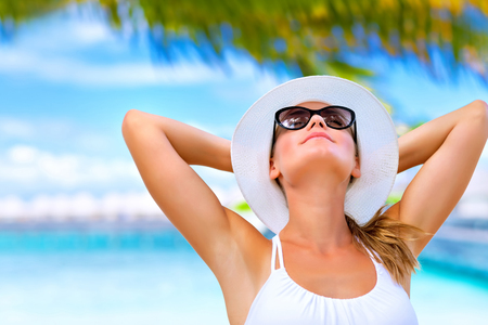 Portrait of young attractive female with hands behind head taking sunbath on the beach, summer vacation on Maldives photo