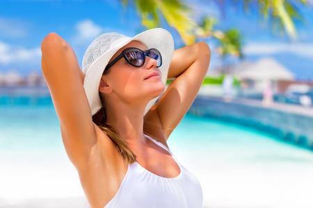 Close-up portret van mooie meisje met de handen achter het hoofd van zonlicht geniet, looien op tropisch strand, luxe kuuroord, reis-en toerisme-concept