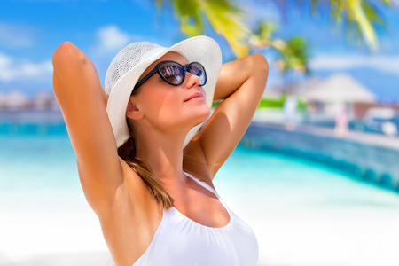 Closeup portrait of pretty girl with hands behind head enjoying sunlight, tanning on tropical beach, luxury spa resort, travel and tourism concept  photo
