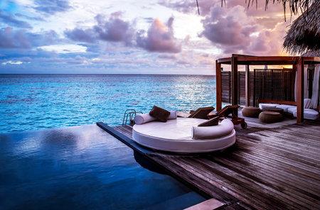 熱帯の島、夏の休暇の概念に夕方の贅沢なビーチ リゾート、海の夕日に無限のプール近くのバンガロー