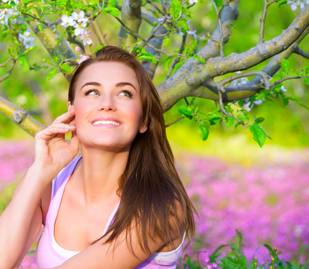 spring time: Closeup portrait of happy woman in blooming garden, having fun outdoors, sitting down on pink floral meadow, spring time concept