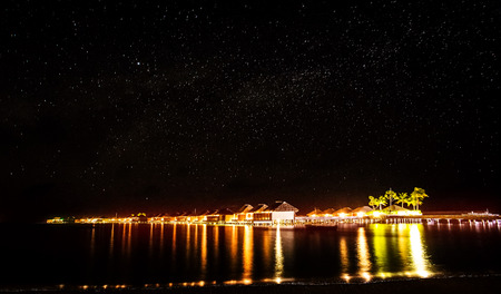 Night on tropical resort, many little beach houses glowing bright yellow lights in dark night, starry sky over sea, romantic summer holidays concept photo