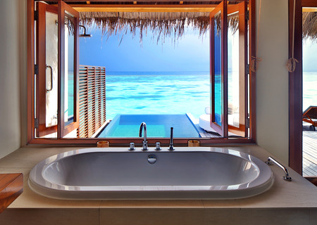 Luxury beautiful interior design on beach resort, window view from bathroom on clear blue sea, summer vacation on Maldives