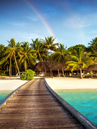 Wooden bridge to island beach resort, beautiful colorful rainbow over fresh green palm trees, luxury hotel on Maldives island, summer vacation concept