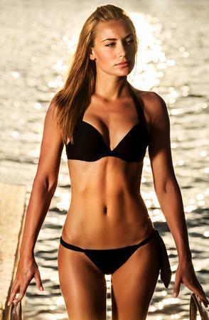 Modelo de moda con rostro serio teniendo tomar el sol en la playa, perfecto cuerpo sexy, vestido con elegante traje de baño negro, concepto de las vacaciones de verano Foto de archivo