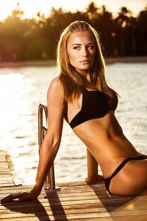 yellow bikini: Sexual woman tanning on the beach in mild sunset light, fashionable model posing for luxury magazine, summertime photo shoot concept Stock Photo