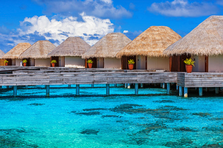 Luxury beach resort on Maldives, many cute bungalows standing on transparent water, Indian ocean, romantic place for honeymoon, summer vacation concept