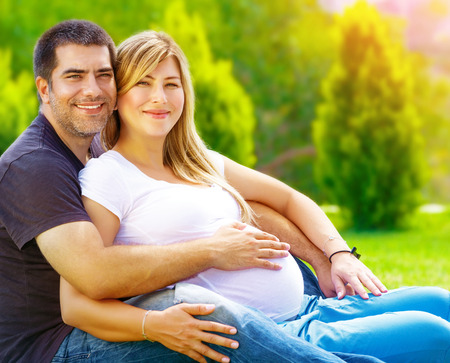 Handsome man with pregnant wife relaxing outdoors, happy parenthood, summer weekend, togetherness and support concept photo