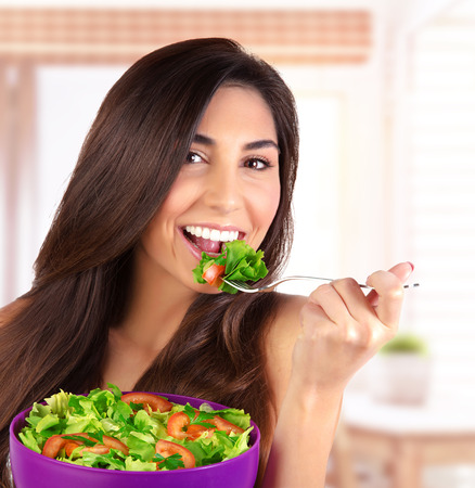 Closeup portrait of beautiful brunette woman eating salad at home on the kitchen, organic food, healthy lifestyle, dieting concept photo