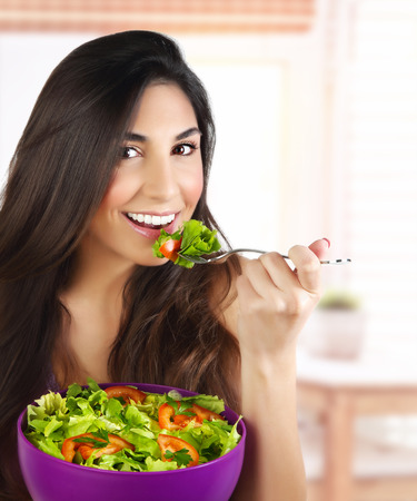 Picture of pretty woman eating green salad, closeup portrait of brunette female holding bowl with fresh vegetables on the kitchen, healthy lifestyle, organic nutrition, dieting concept Stock Photo - 27639339