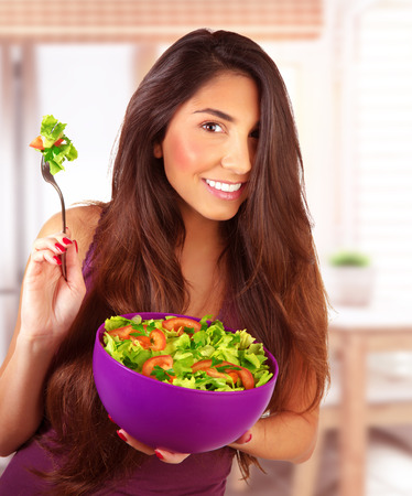 Sportive girl eating fresh vegetarian salad at home in the kitchen, loss weight, healthy nutrition, body care and beauty concept Stock Photo - 27639342