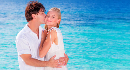 Happy couple kissing on the beach, young family in love spending honeymoon vacation on an islands, cheerful active young people having fun at summer travels, joy of life concept photo