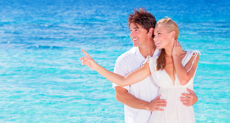 Happy couple enjoying beach, young family in love spending honeymoon vacation on luxury islands, cheerful active young people having fun at summertime travels, joy of life concept photo
