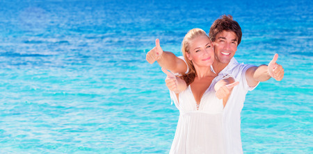 Happy couple on the beach, young family in love spending honeymoon vacation on luxury islands, cheerful active young people having fun at summertime travels, joy of life concept photo
