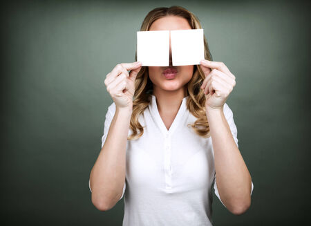 Portrait of cute blond girl closes her eyes with two blank cards isolated on grey background, copy space, place for romantic advertisement  photo