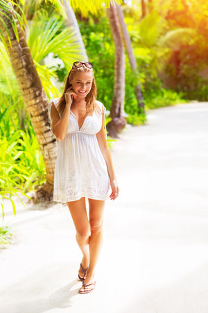 indian summer: Pretty woman walking along tropical beach, summer vacation on Maldives island, enjoying exotic nature, travel and tourism concept