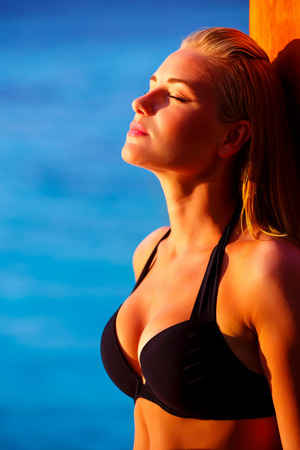 sea sexy: Closeup portrait of sexy woman tanning on the beach, bright sun light, fashionable model posing near sea, travel and tourism concept
