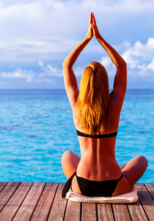 phisical: Rear view of sexy female doing yoga outdoors in warm sun light near the sea, phisical exercise for clearing mind, healthy lifestyle, peace and harmony concept  Stock Photo