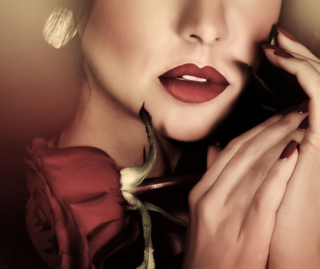 Closeup retro style photo of beautiful woman, half of face, sexy red lips and red rose in hands, passion and sensuality concept  Stock Photo - 27821984