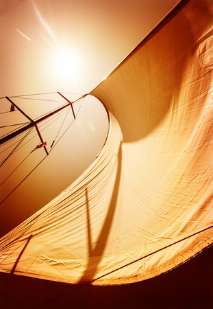 Sail fluttering in the wind on orange sky background, mild sunset light, sea cruise on luxury sailboat, summer vacation and holidays concept photo