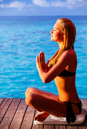 Woman meditating on the beach, doing exercise on wooden deck over blue sea, summer vacation, yoga and relaxation concept photo