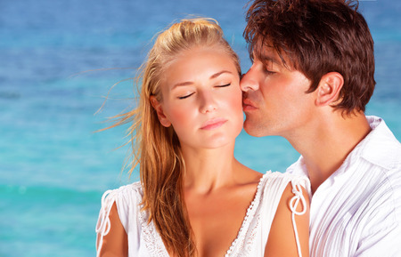 Romantic couple kissing on the beach, close-up faces portrait of two in love, young people relaxing outdoor on summer holidays on Maldives islands, family on honeymoon vacation photo