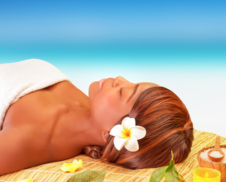 Attractive American female sleeping on massage table on the beach, enjoying day spa, luxury summer traveling concept photo
