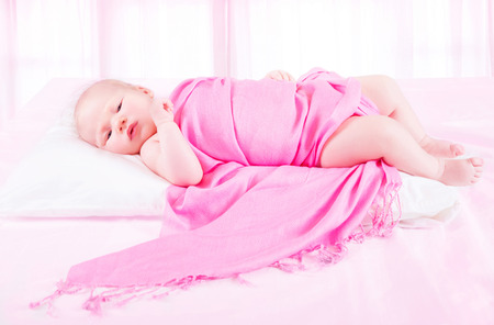 Adorable baby girl lying down in childs bedroom wrapped in beautiful pink blanket, carefree childhood, bedtime concept photo