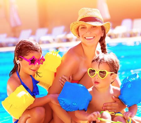 beach resort: Familia feliz en vacaciones de verano, la joven madre con dos ni�os lindos que se divierten cerca de piscina en centro tur�stico de playa, el amor y el concepto de amistad
