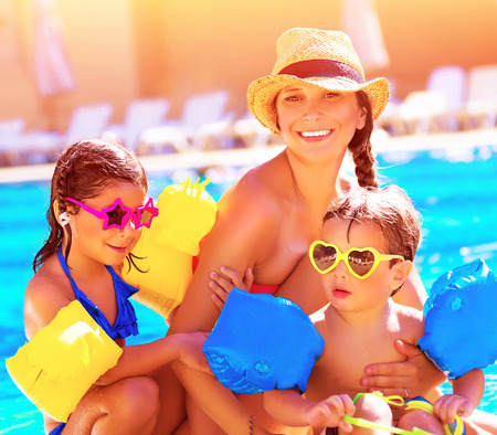 Happy family in summer vacation, young mother with two cute kids having fun near swimming pool on beach resort, love and friendship concept