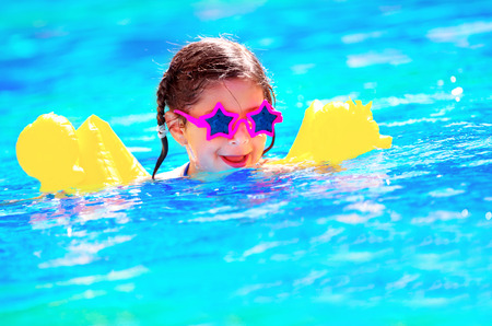 Cute little baby swimming in the pool, wearing funny sunglasses, enjoying summer weekend in aquapark, holidays and vacation concept photo