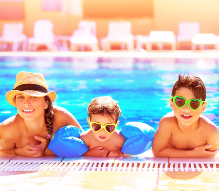 aquapark: Portrait of happy cheerful family having fun in aquapark, swimming in the pool, relaxing in luxury summer resort, holidays and vacation concept Stock Photo