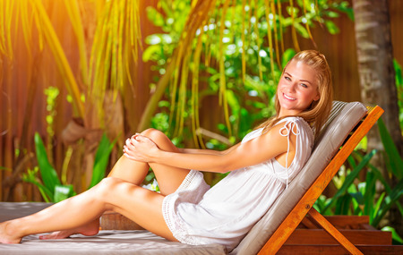 Cute female on tropical resort, sitting on deckchair and taking sun bath, enjoying exotic nature, summer vacation on Maldives photo