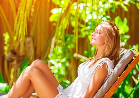 Cute female on tropical resort, sitting on deckchair with closed eyes and taking sun bath, enjoying exotic nature, summer vacation on Maldives  photo