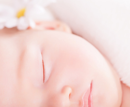 Closeup portrait of cute little baby sleep, face part, gentle daisy flower decoration, carefree childhood, purity and innocence concept photo