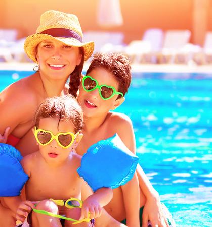 夏休み、楽しんでビーチ リゾート、愛と友情の概念にはスイミング プールの近く 2 つのかわいい子供を持つ若い母親の幸せな家族