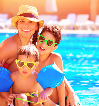 pool fun: Happy family in summer vacation, young mother with two cute kids having fun near swimming pool on beach resort, love and friendship concept