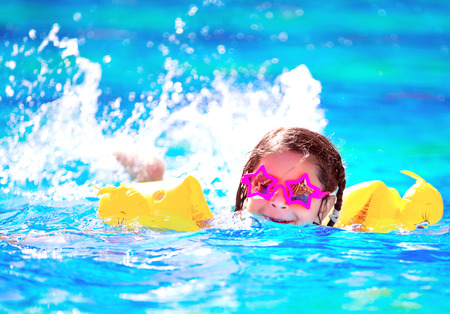 Cute little baby swiming in the pool, wearing funny sunglasses, enjoying summer weekend in aquapark, holidays and vacation concept