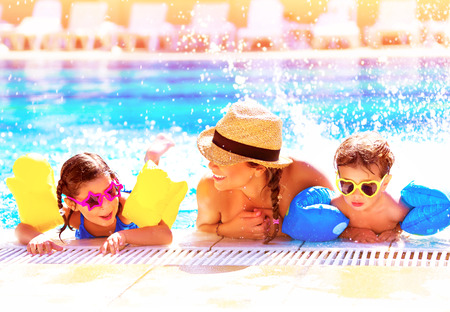 baby swimming: Portrait of happy cheerful family having fun in aquapark, swimming in the pool, relaxing in luxury summer resort, holidays and vacation concept Stock Photo