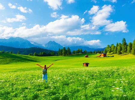 Gelukkig reiziger meisje in bergachtige vallei, genieten van de natuur met opgeheven handen omhoog, wandelen langs alpiene bergen, zomervakantie concept