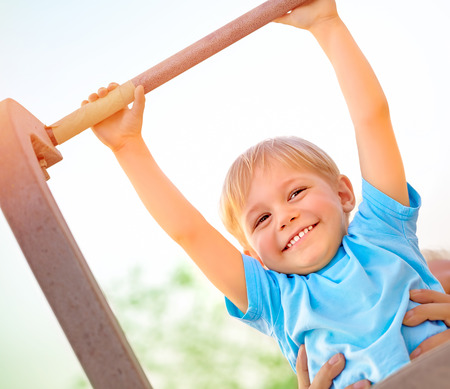 Little boy with fathers help catch up on the horizontal  bar, active childhood, cute small acrobat, workout on backyard, summer camp concept photo