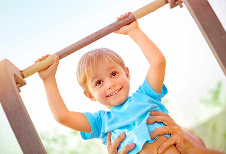 Closeup portrait of little happy boy lifting on crossbar, daddy help his son doing physical exercise outdoors, happy and healthy childhood concept photo
