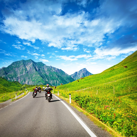 rout: Group of motorcyclists on countryside in mountains, traveling along Alpine mountains, extreme sport, driving along cow pasture