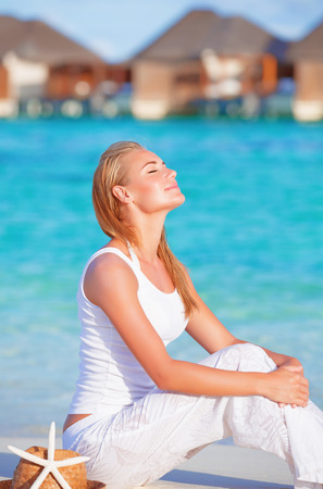 Pretty woman sitting on the beach with closed eyes under warm bright sun lights, spending summertime on Maldives  Stock Photo
