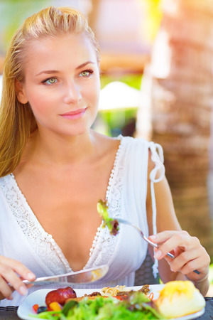 Closeup portrait cute blond girl sitting in outdoors restaurant and having breakfast, eating fresh vegetables salad, luxury healthy eating concept  Imagens