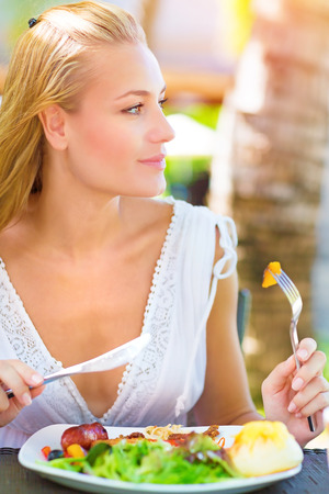 Closeup portrait cute blond girl sitting in outdoors restaurant and having breakfast, eating fresh vegetables salad, luxury healthy eating concept  photo